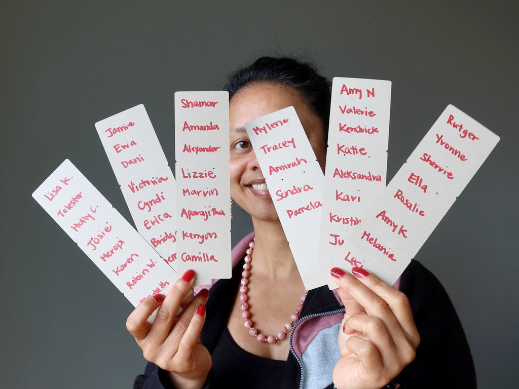 sheila of satin crystals holding up 6 strips of paper with contestant names written down