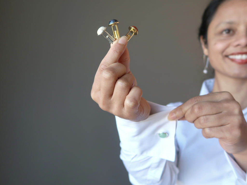 woman holding three gemstone cufflinks