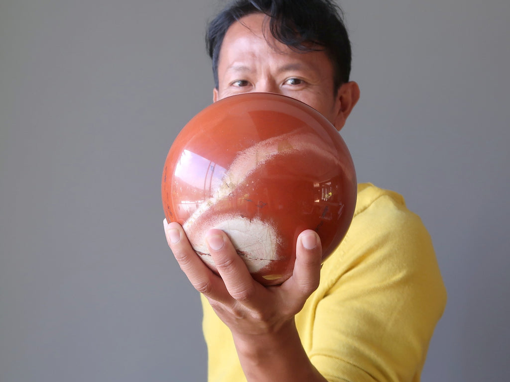 man holding a large red jasper sphere
