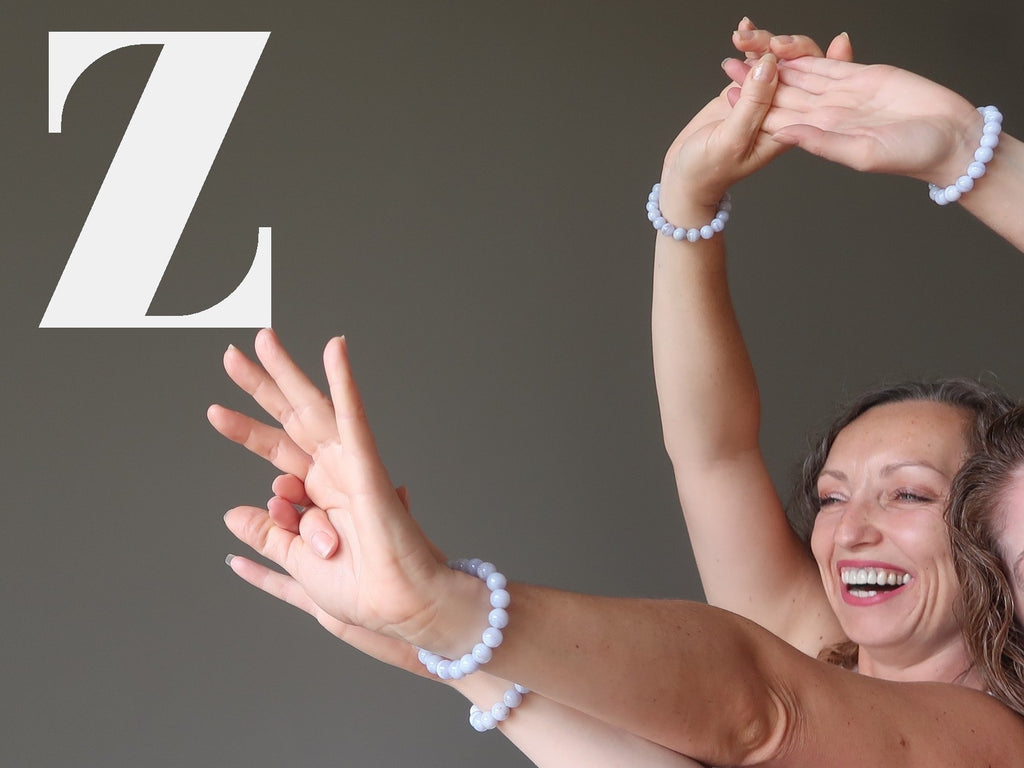 Zodiac bracelets: aleks and jamie of satin crystals with arms raised in a happy dance together
