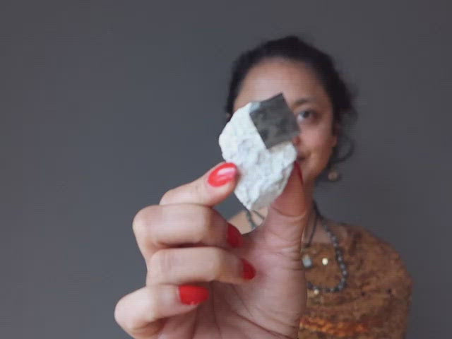 video on hand holding pyrite cube on white matrix