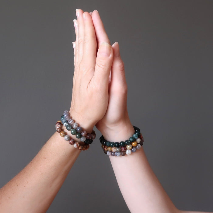 hands high fiving wearing botswana, crazy lace and moss agate round beaded stretch bracelet sets