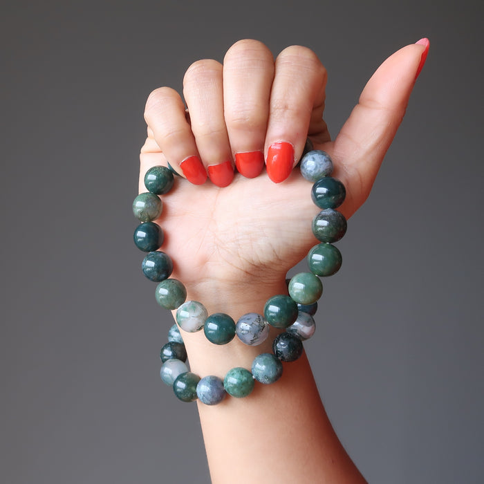 hand holding and wearing green and white moss agate round beaded stretch bracelets