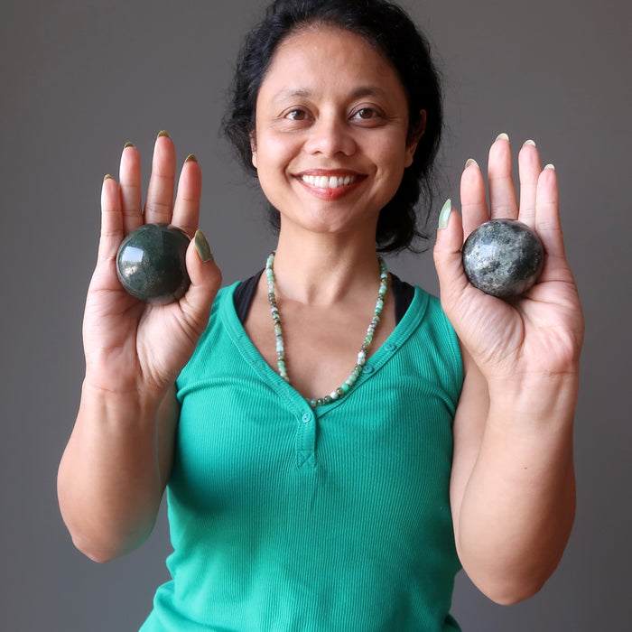 sheila of satin crystals holding moss agate spheres in each palm
