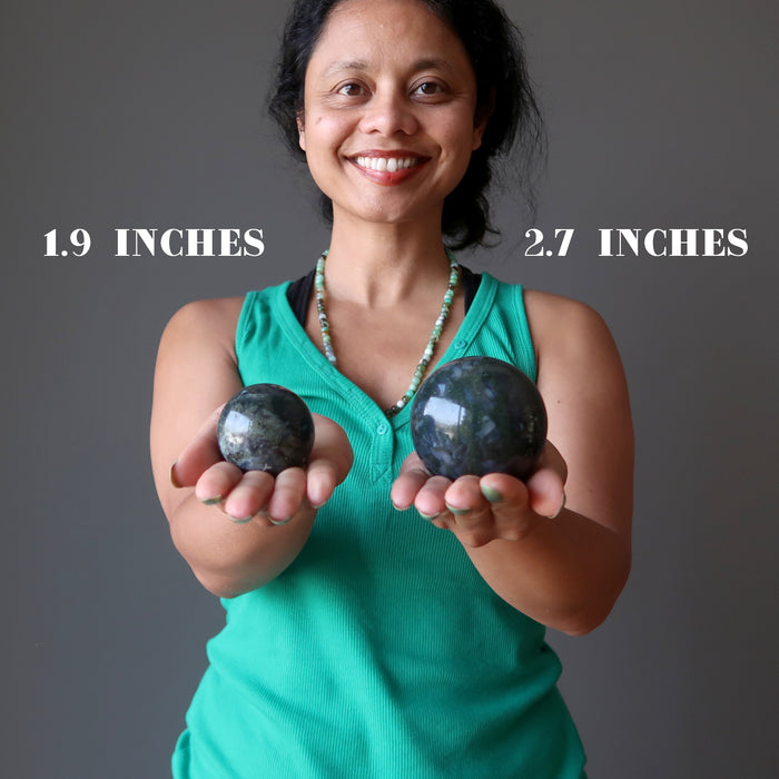 sheila of satin crystals holding 1.9 inch and 2.7 inch moss agate spheres to show size difference