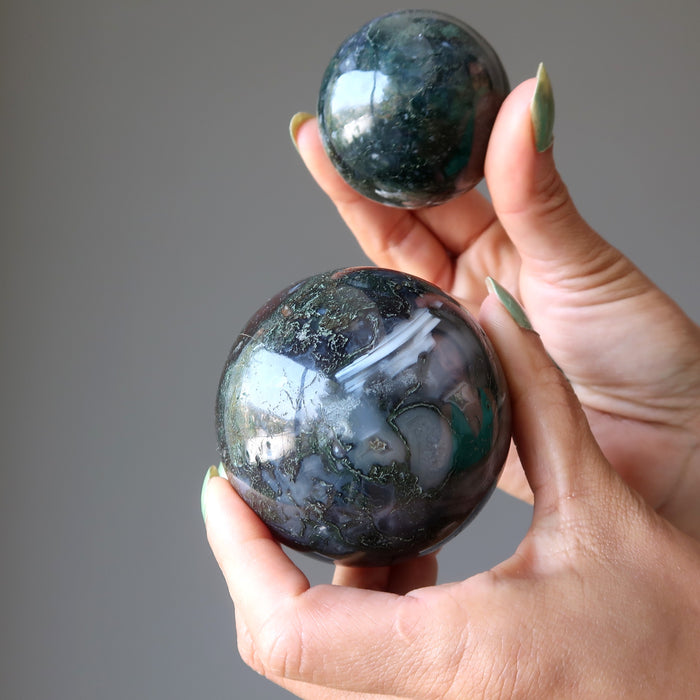 two hands holding a moss agate ball in each