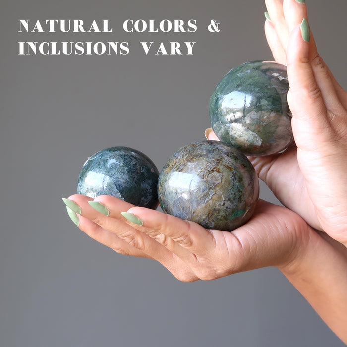 hand holding moss agate spheres to show natural colors and inclusions vary