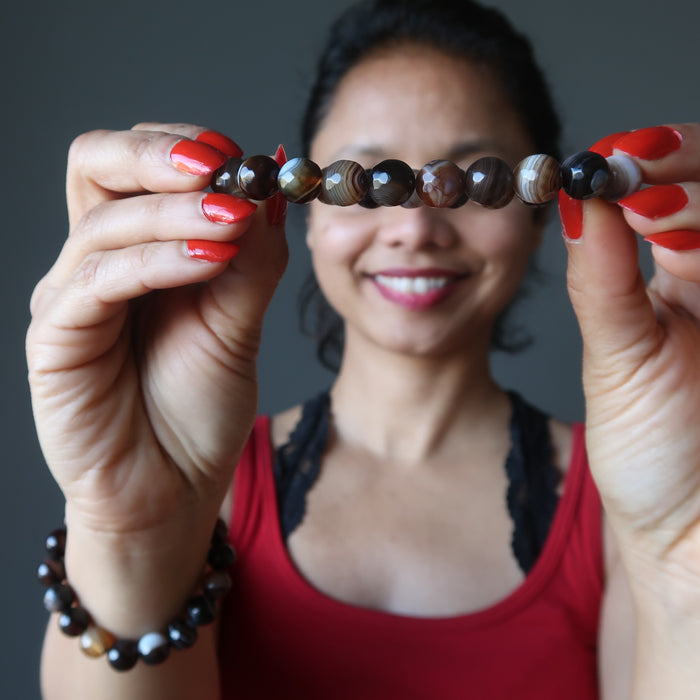 sheila of satin crystals wearing and holding up banded coffee brown and black agate faceted round beaded stretch bracelets