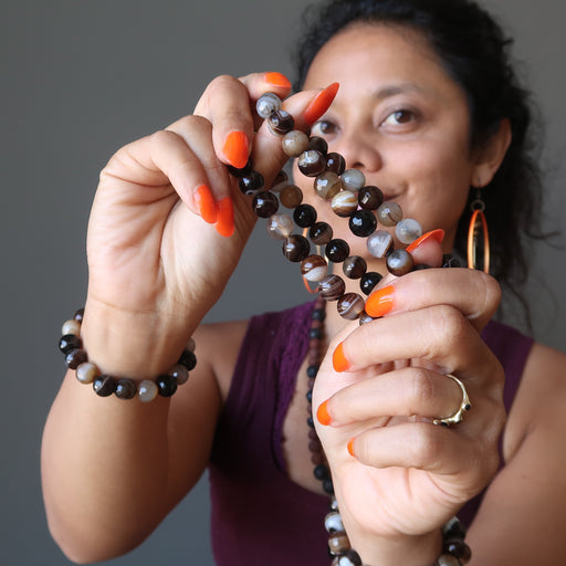 sheila of satin crystals wearing and holding banded coffee brown and black agate faceted round beaded stretch bracelets