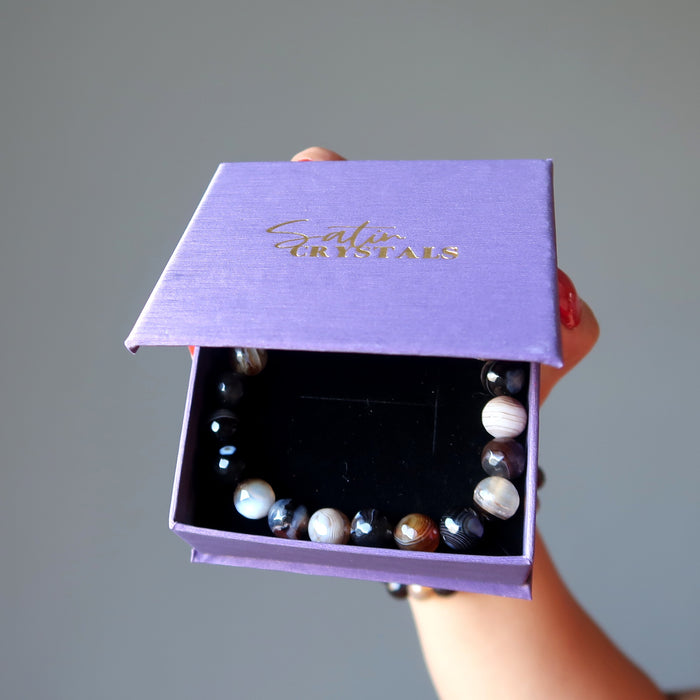 hand holding banded coffee brown and black agate faceted round beaded stretch bracelets in a purple satin crystals gift box