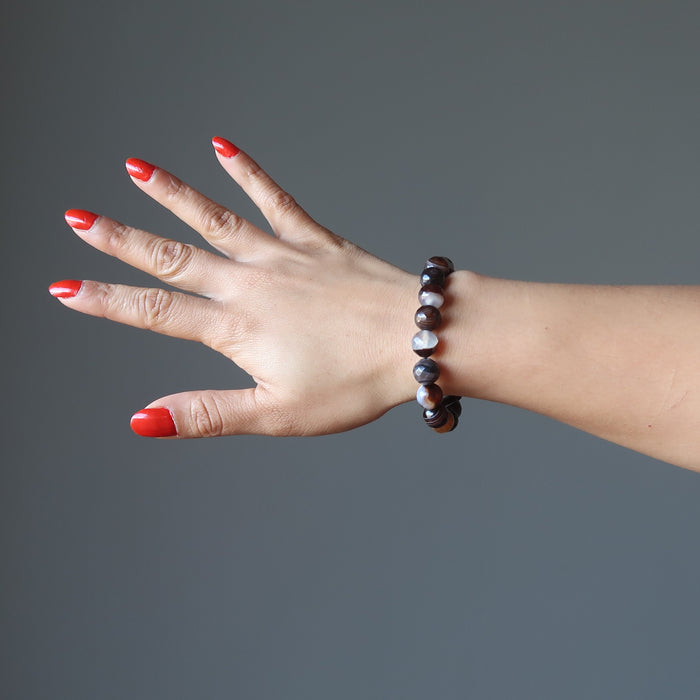 hand wearing banded coffee brown and black agate faceted round beaded stretch bracelets
