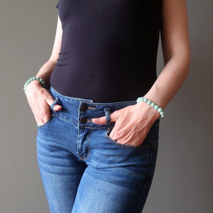 female model with both hands in jean pockets wearing amazonite bracelets