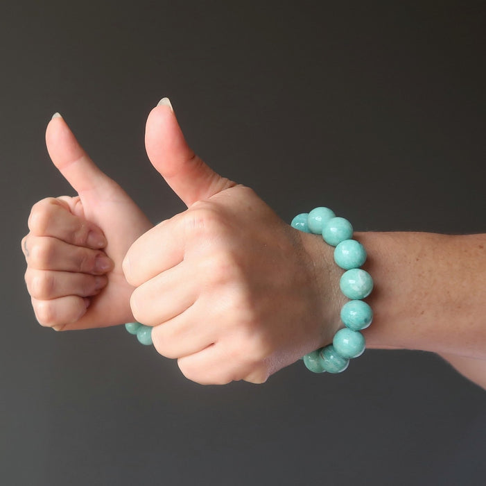 two thumbs up wearing amazonite bracelets on wrists
