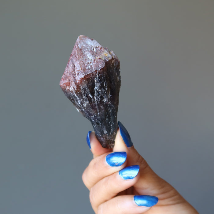 hand holding raw super 7 amethyst crystal point