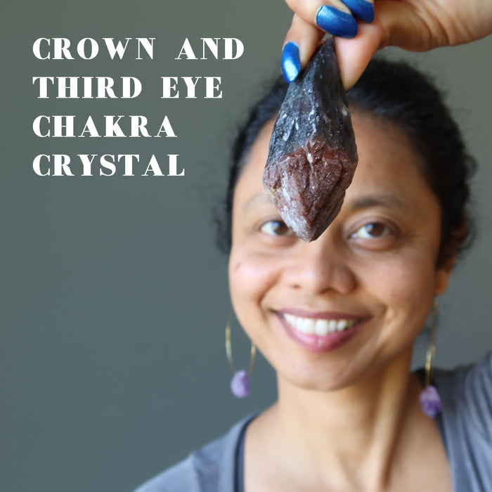 sheila of satin crystals holding raw super 7 amethyst crystal point over her crown and third eye chakra