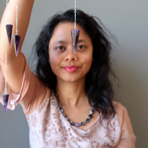 sheila of satin crystals holding an amethyst pendulum