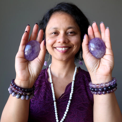sheila of satin crystals holding pair of purple amethyst polished ovalish palm stones
