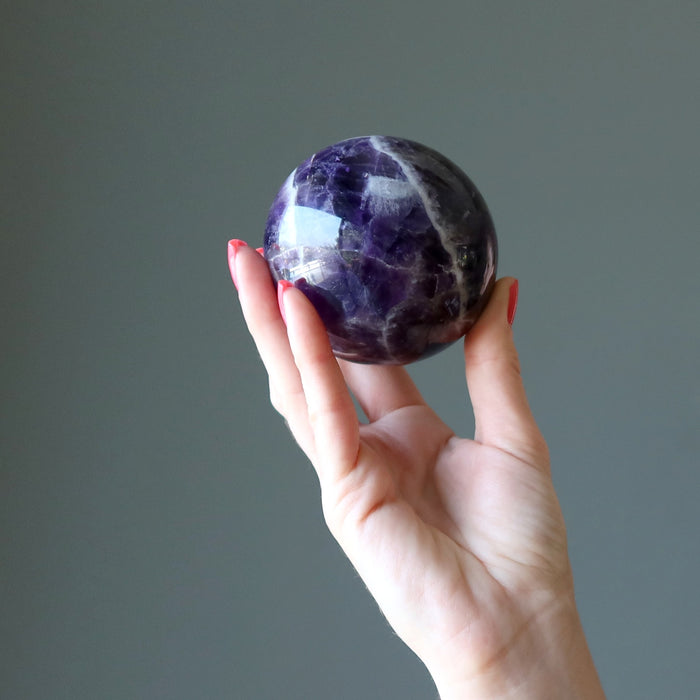 hand holding up a chevron amethyst sphere