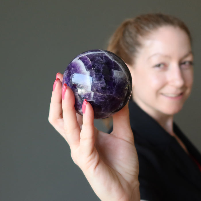 jamie of satin crystals holding up a chevron amethyst sphere