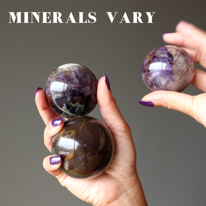 hand holding 3 amethyst mineral mania spheres to show minerals vary
