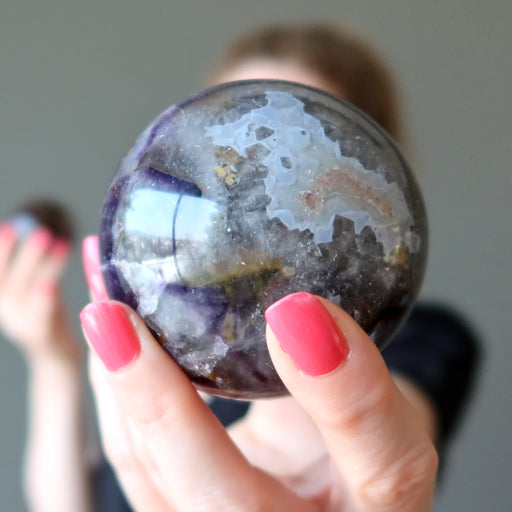 hand holding amethyst mineral mania sphere