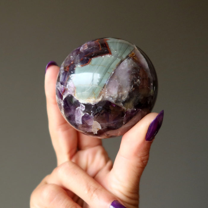 hand holding mineral amethyst sphere