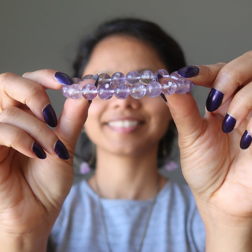 Sheila Satin of Satin Crystals holds out a clear purple Ametrine stretch bracelet