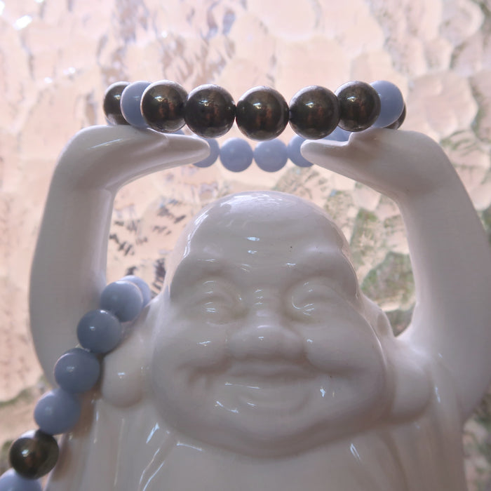 angelite pyrite stretch bracelet on white laughing buddha statue