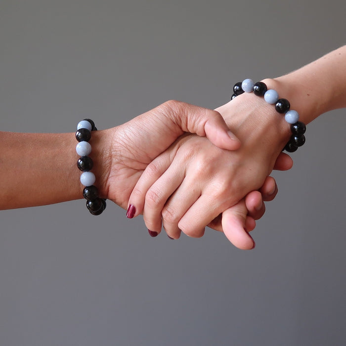 man and woman holding hands wearing rainbow obsidian angelite bracelets