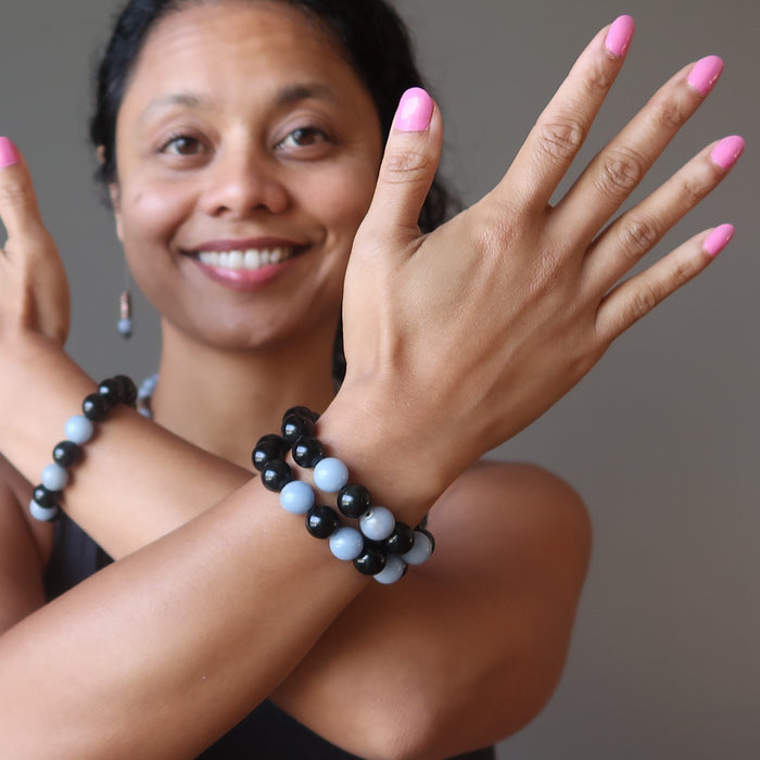 sheila of satin crystals wearing blue angelite and black rainbow obsidian stretch bracelets