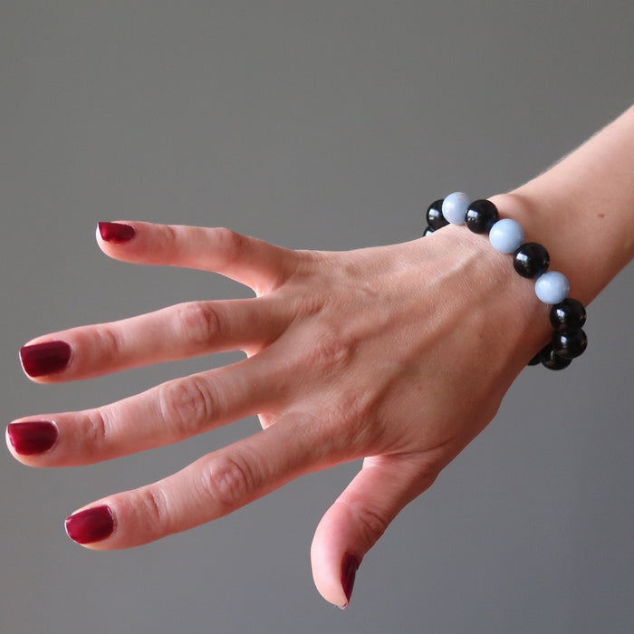female hand modeling blue angelite and black rainbow obsidian stretch bracelet