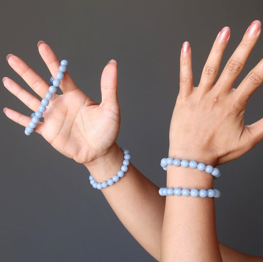 two hands wearing blue angelite round beaded stretch bracelets
