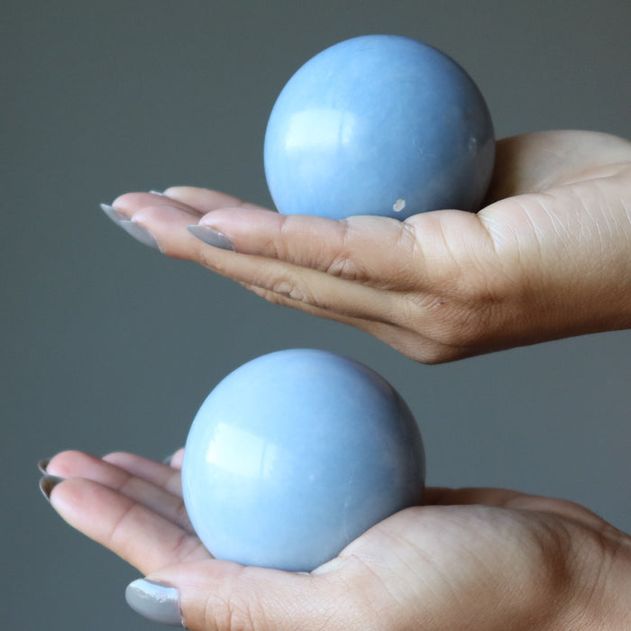 palms of hands holding angelite spheres in each