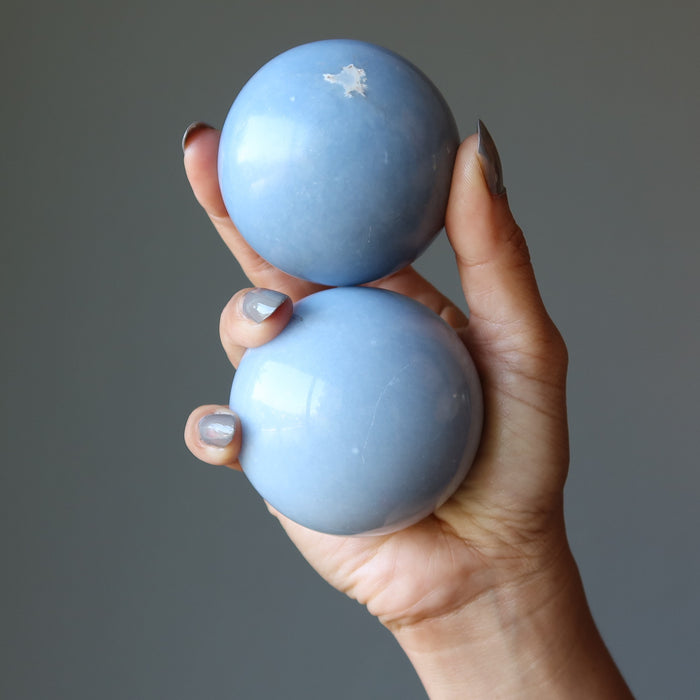 hand holding two angelite spheres
