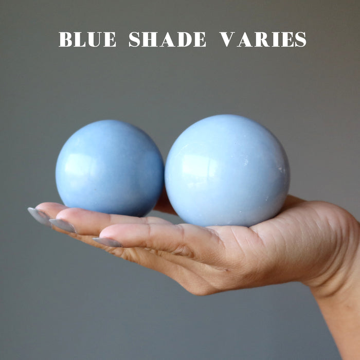 hand holding two angelite spheres showing blue shade varies