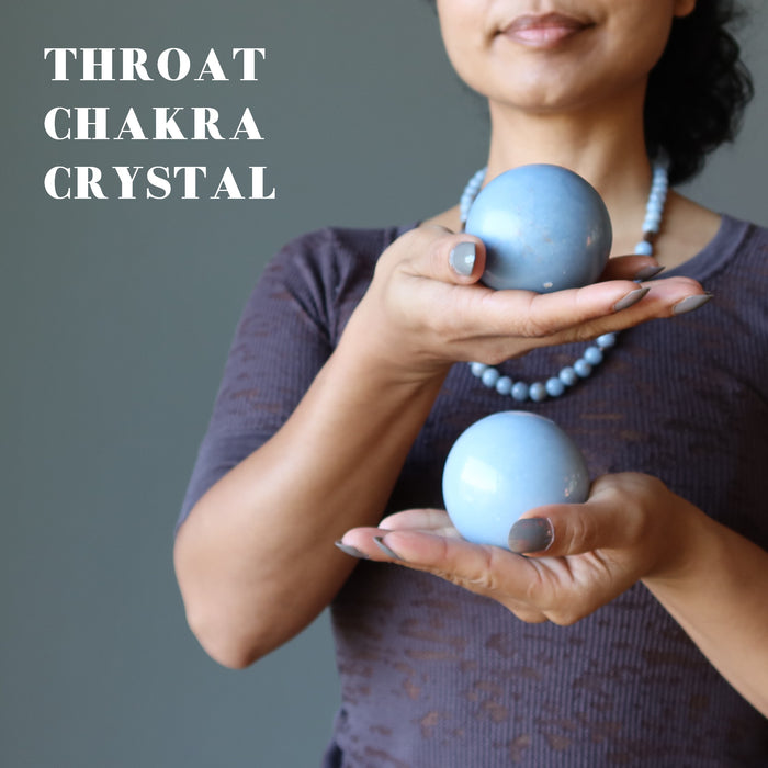 sheila of satin crystals holding two angelite spheres at the throat chakra