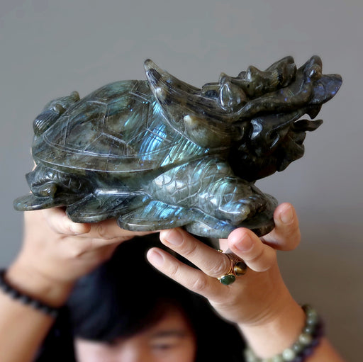 lydia of satin crystals holding a big labradorite dragon turtle carving over her head