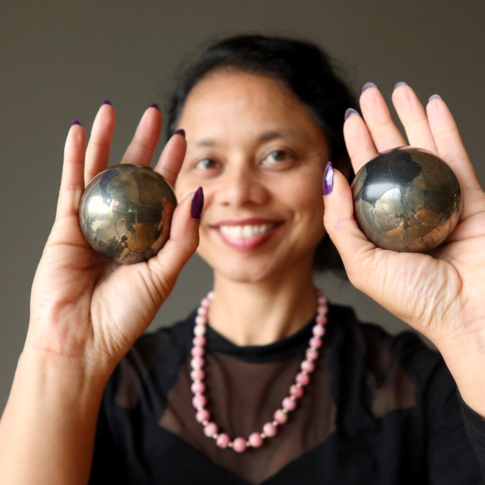 sheila of satin crystals holding two apache gold spheres in her palms