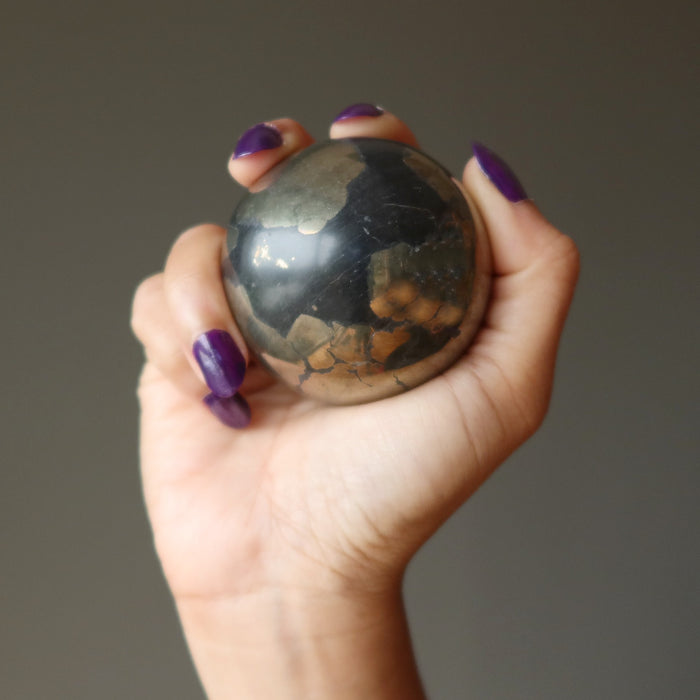 hand holding gold and black apache gold sphere