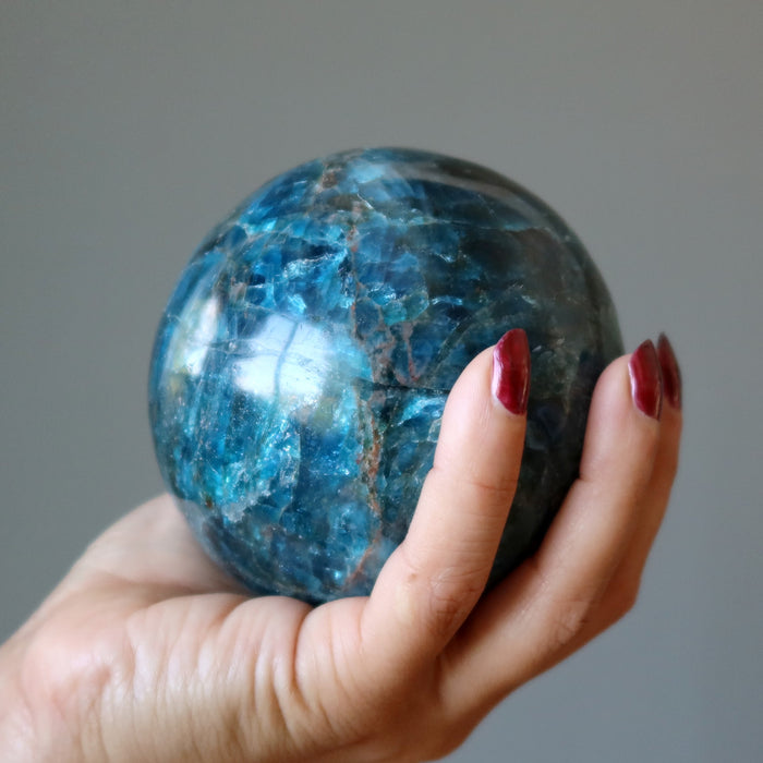 hand holding up an apatite sphere