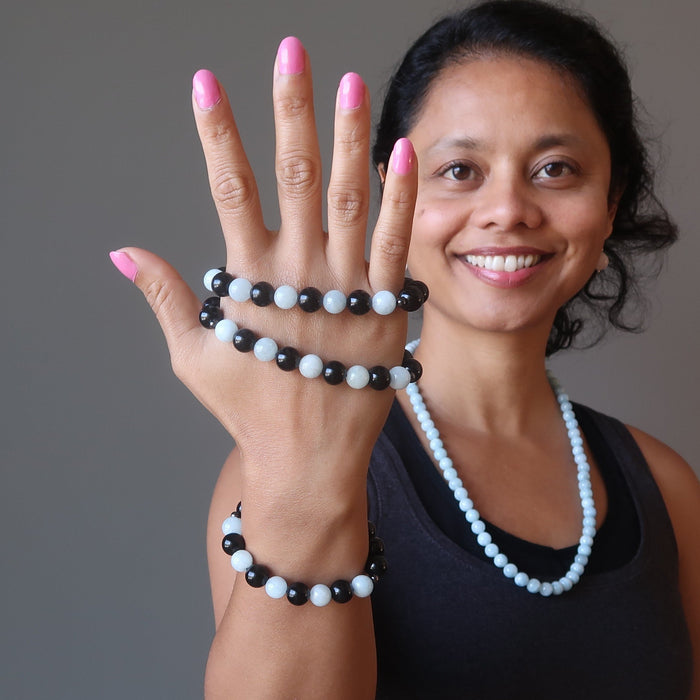 sheila of satin crystals holding up blue aquamarine and black rainbow obsidian stretch bracelets