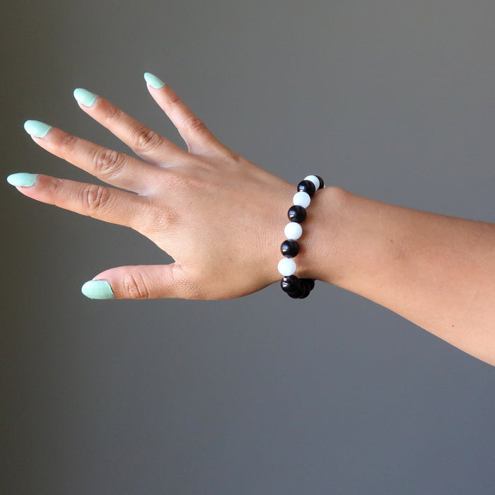 woman's hand wearing blue aquamarine and black rainbow obsidian stretch bracelet