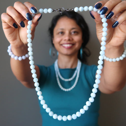 sheila of satin crystals holding out a blue aquamarine necklace