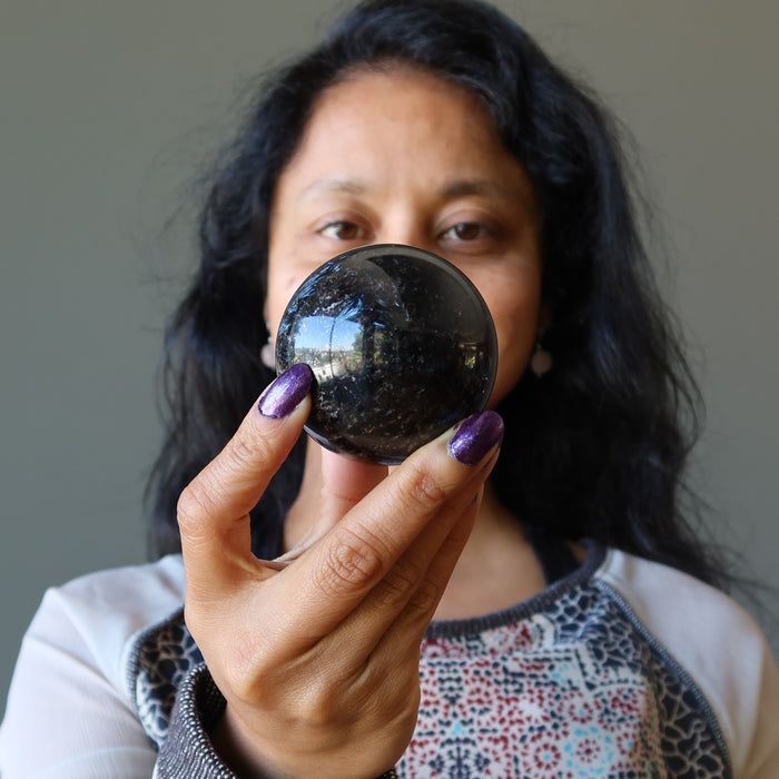 sheila of satin crystals holding an arfvedsonite sphere