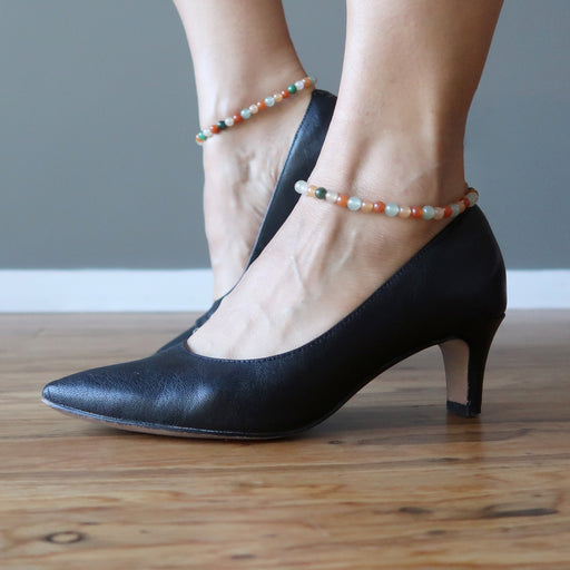 feet in black heels wearing multi-colored aventurine anklets