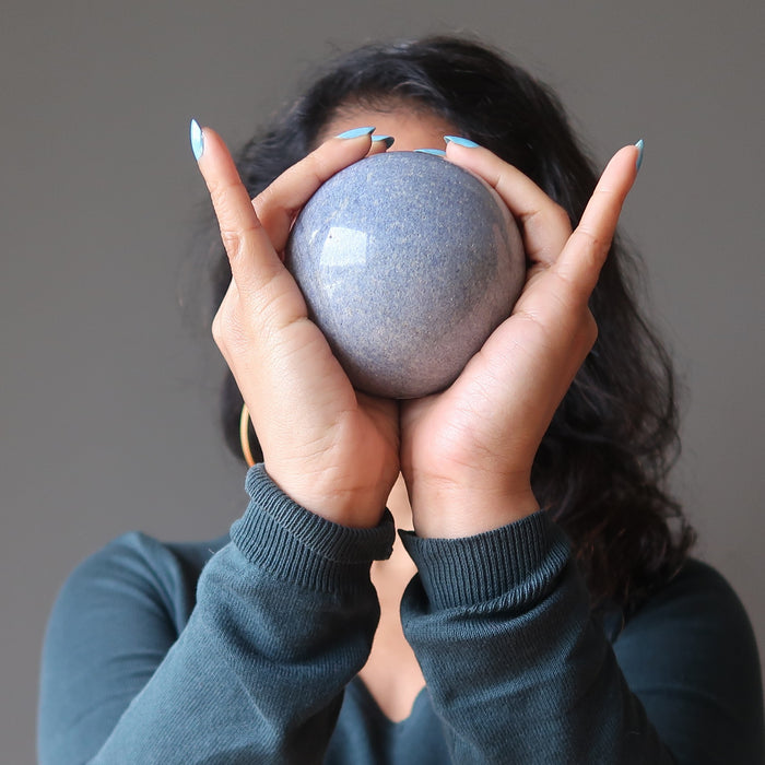 sheila of satin crystals holding a blue aventurine sphere in front of her face