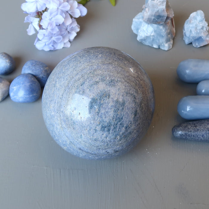 blue aventurine sphere surrounded by blue stones and flowers