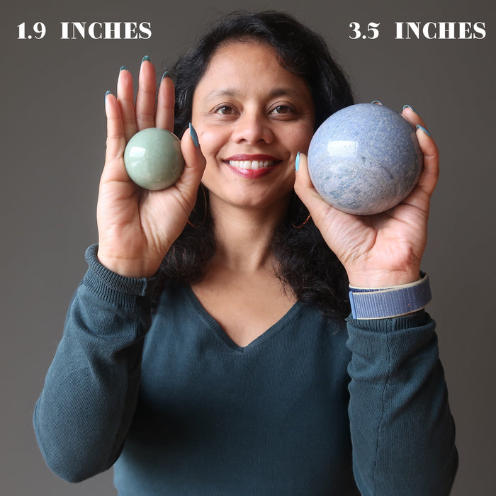 sheila of satin crystals holding a green aventurine and a blue aventurine sphere in each hand showing size differences