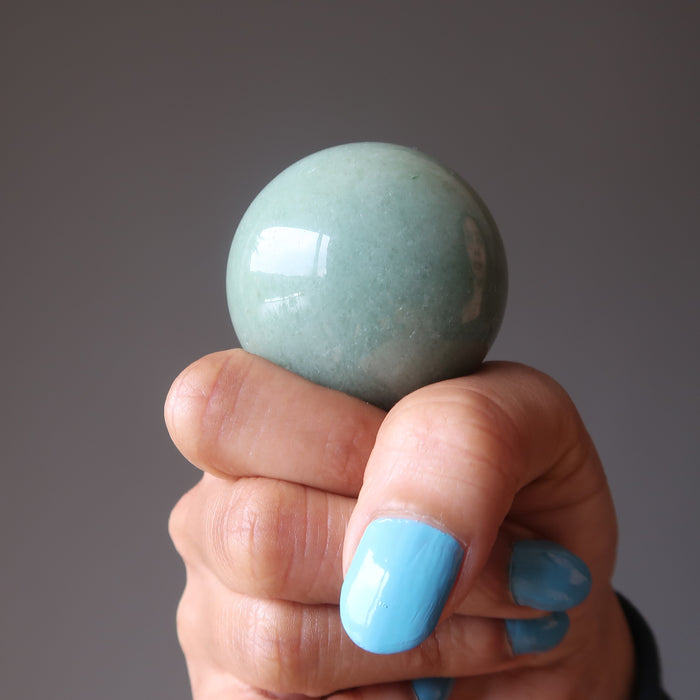 hand with green aventurine crystal ball