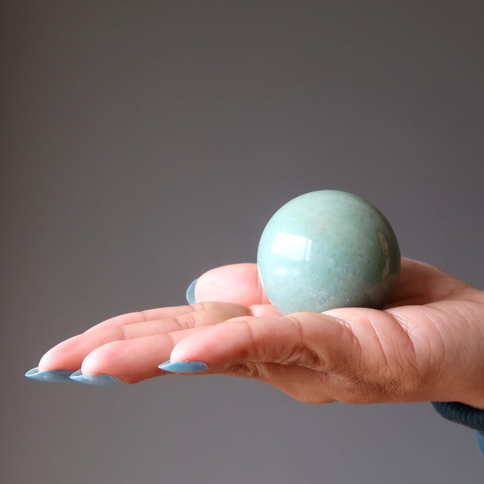 palm of hand in green aventurine crystal ball